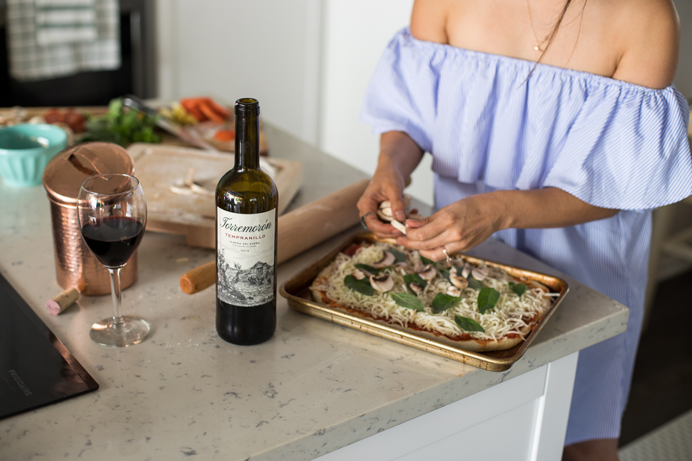 Lifestyle blogger Devin McGovern and wife Marlene Martinez in the kitchen with pizza and wine